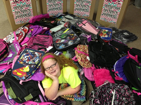 "Kamrie in the middle of the 144 backpacks that she got donated for ""Operation Backpack Happiness"". She was able to provide 66 backpacks to foster kids and the rest she donated to kids at Dover Elementary and Dardanelle Elementary and then donated the remaining 30 backpacks to The CALL in Pope County."