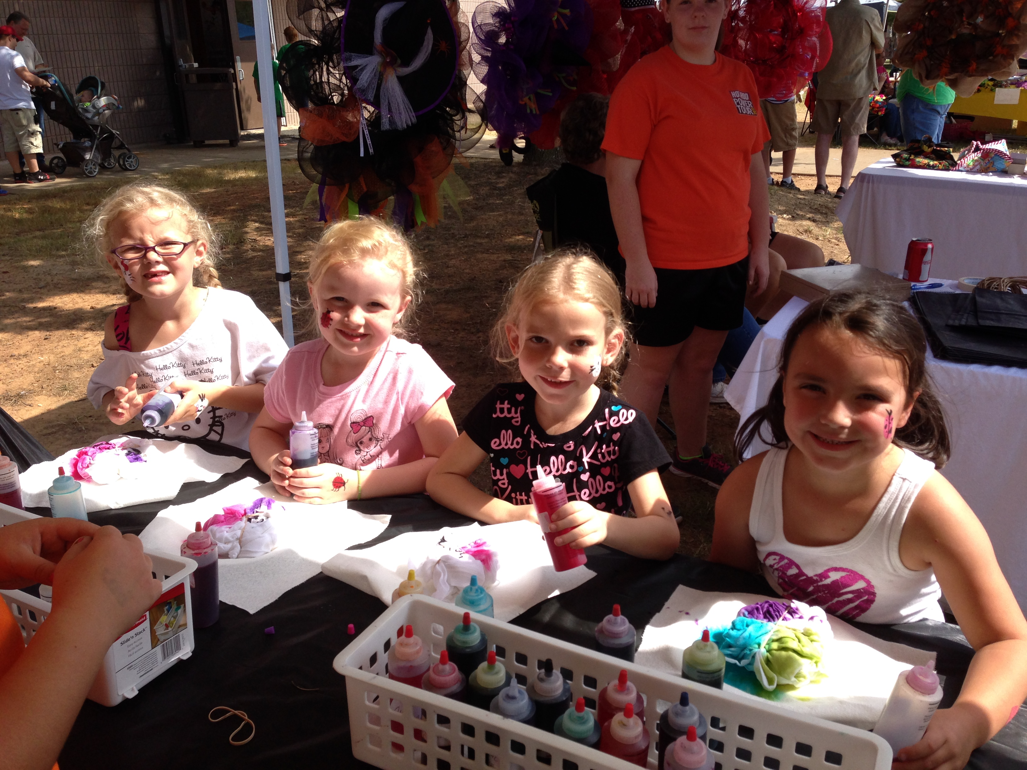 Four little girls who came to Kamrie's booth to tye-dye shirts to help raise money for suitcases on wheels for foster kids